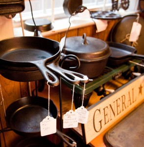 A stack of skillets are seen alongside an antique gas stove with an antique Dutch oven.